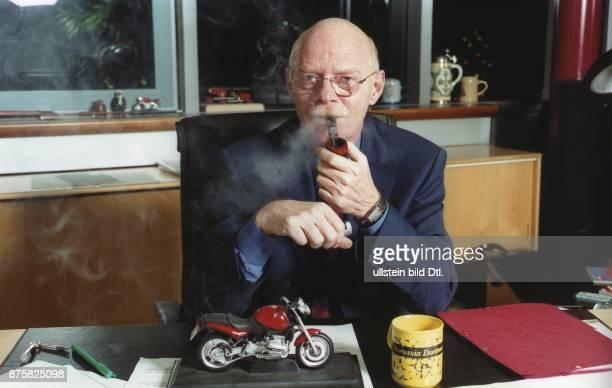 Der SPDPolitiker Dr Peter Struck Bundestagsfraktionsvorsitzender sitzt Pfeife rauchend in seinem Arbeitszimmer am Schreibtisch Auf dem Tisch befinden...