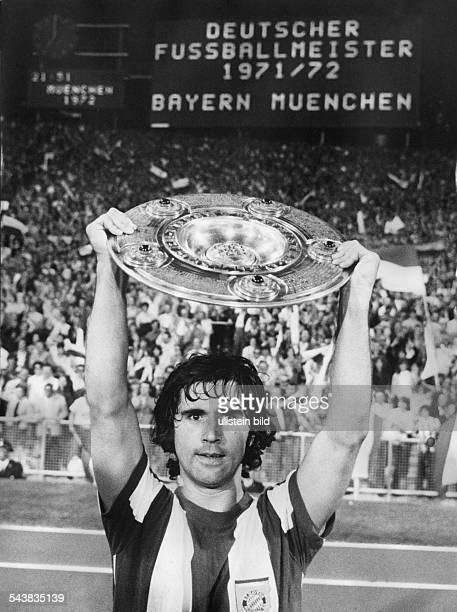Der Stürmer von Bayern München Gerd Müller hält nach dem Gewinn der deutschen FußballMeisterschaft am im Münchener Olympiastadion triumphierend die...