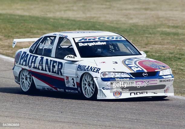 Der Tourenrennfahrer Alexander Burgstaller in seinem Opel auf der Rennstrecke Sein Fahrzeug ist versehen mit Werbung für Paulaner und ARCOR...