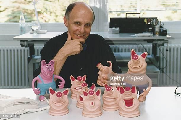 Der Trickfilmer Alexander Zapletal sitzt das Kinn in die Hand gestützt an einem Tisch auf dem verschiedene Schweinefiguren stehen