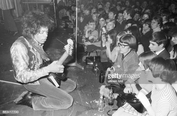Der USamerikanische RockGitarrist und Sänger Jimi Hendrix bei einem Konzert in Hamburg Er kniet auf der Bühne vor der Bühne Zuschauer