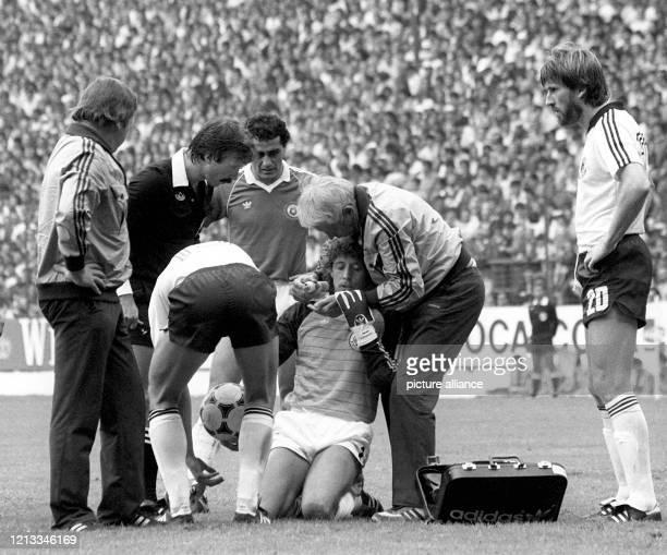 Der verletzte deutsche Torhüter Harald Schumacher kniet am Boden und wird von Massseur Erich Deuser gepflegt. Schumachers Vordermann Manfred Kaltz ,...