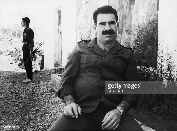 Der Vorsitzende der PKK Abdullah Öcalan sitzt vor einem Gebäude Im Hintergrund steht ein Mann mit einem Gewehr Aufgenommen September 1991