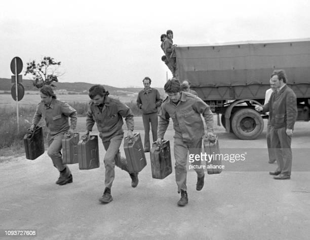 Der Wettlauf mit gefüllten Benzinkanistern ist Teil der GST-Bestenermittlung bei den Militärkraftfahrern, aufgenommen in Roßleben im Jahre 1974. -...