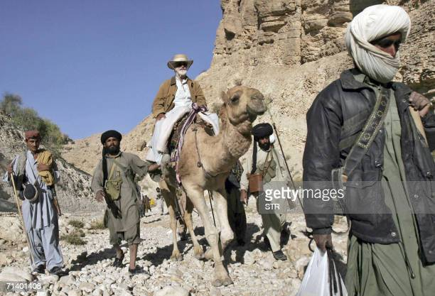 In this recent undated picture chief of a Pakistani rebel tribe Nawab Akbar Bugti rides on a camel along with his tribe guards in the mountains of...