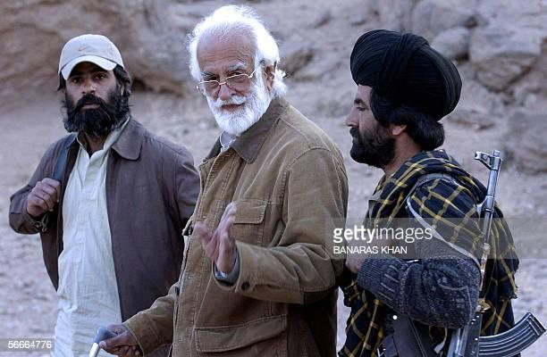 Pakistani Bugti tribal leader Nawab Akbar Bugti walks with armed gaurds in the remote mountainous area of Dera Bugti in Pakistan's southwestern...