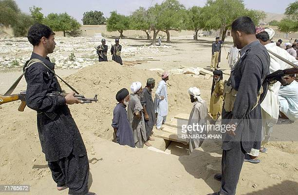 Pakistani paramilitary soldiers stand guard while tribal men bury rebel tribal chief Nawab Akbar Bugti after his funeral in the remote town of Dera...