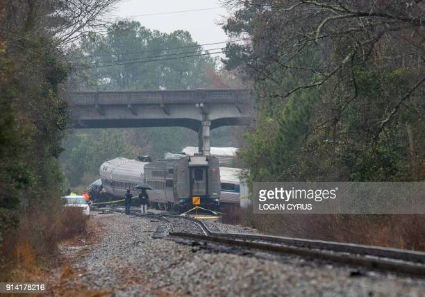 TOPSHOT A derailed Amtrak car can be seen up the tracks near a crossing after an early morning collision with a CSX freight train on February 4 2018...