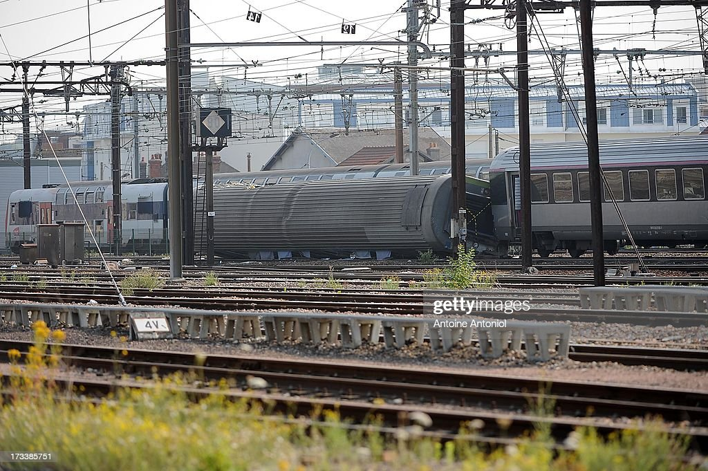 Derailed carriages lie across rail tracks the day following a train accident at Bretigny-sur-Orge railway station on July 13, 2013 in Bretigny-sur-Orge, France. An intercity train carrying 385 passengers, travelling from Paris towards Limoges, derailed crashing into a station platform leaving six people dead and a further 30 injured on July 12, 2013. French investigators for SNCF have stated that the cause by a fault in the tracks.
