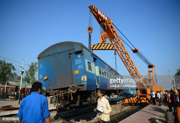 A derailed coach of an Indian express train is lifted by a crane offthe tracks near Manikpur railway station in Uttar Pradesh on November 24 2017...