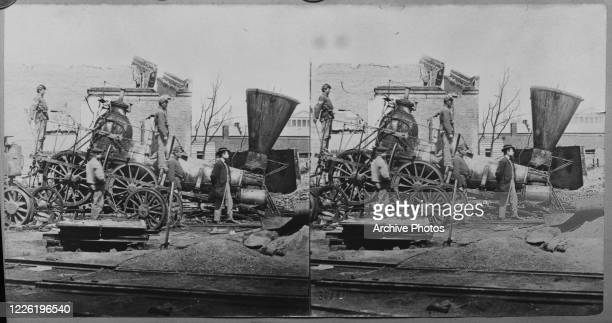 A derailed steam locomotive at the depot of the Richmond and Petersburg Railroad in Richmond Virginia during the American Civil War 1865 The city was...
