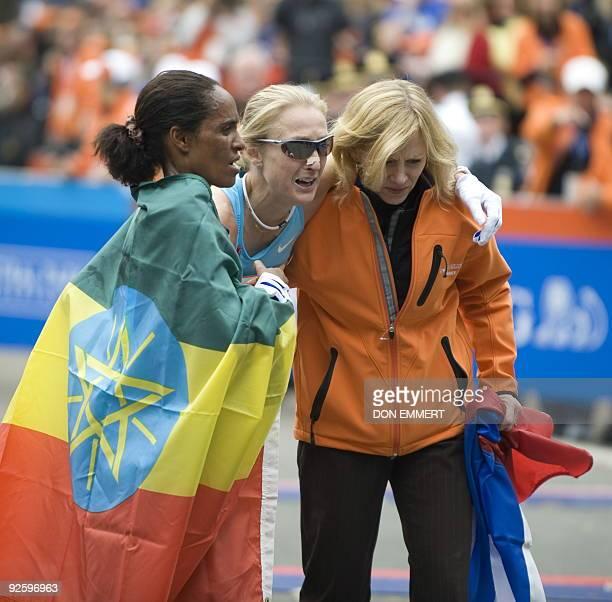Derartu Tulu of Ethiopia and a marathon staff member help Paula Radcliffe of Great Britain at the finish line of the New York City Marathon November...