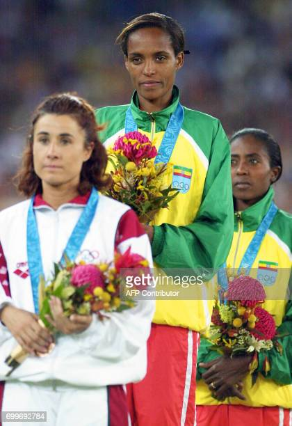 Derartu Tulu of Ethiopia and compatriot Gete Wami flanked by Fernanda Ribeiro of Portugal flash big smiles from the podium during the medals ceremony...