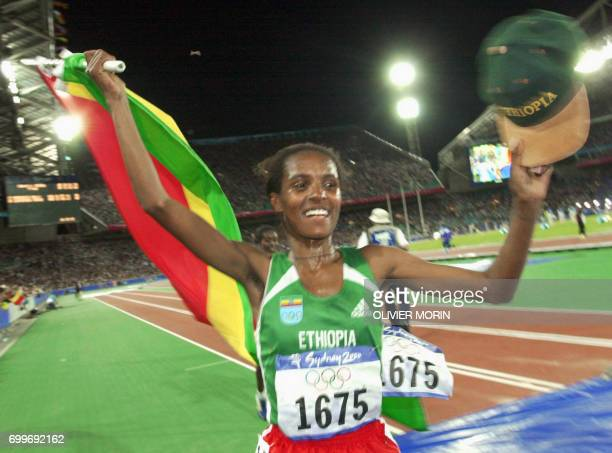 Derartu Tulu of Ethiopia flashes a big smile during the lap of honor 30 September 2000 at the Sydney Olympic Games after winning the Olympic gold...