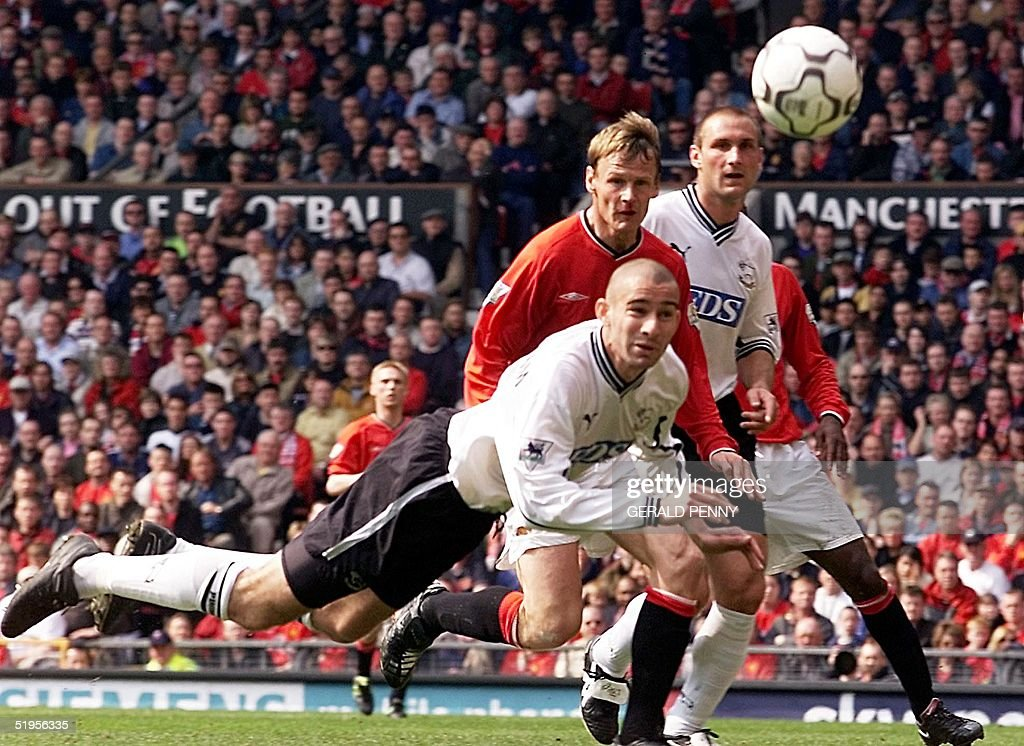 Derby County defender Danny Higginbotham clears with a diving header from Manchester United's David Beckham cross watched by Teddy Sheringham and Horacio Cabonari 05 May 2001, during their Premiership match at Old Trafford.
