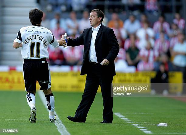 Derby County manager Billy Davies gives water to Paul Peschisolido during the CocaCola Championship match between Derby County and Sunderland at...
