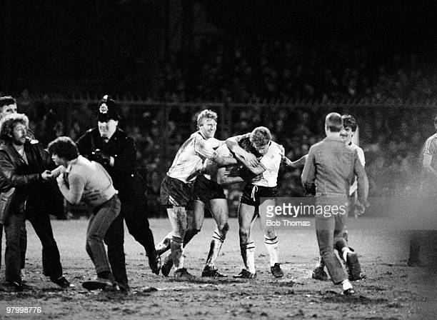 Derby County's George Foster Andy Hill and Ian Dalziel celebrate their victory over Nottingham Forest as the police attempt to clear fans from the...