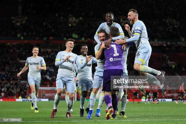 Derby players celebrate with Derby goalkeeper Scott Carson after his penalty save gifted them victory during the Carabao Cup Third Round match...