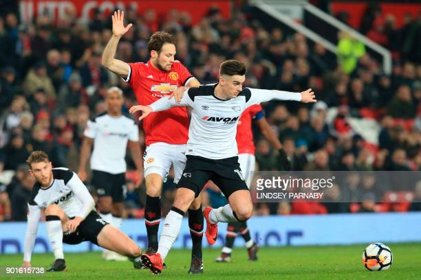 Derby's Welsh midfielder Tom Lawrence holds off Manchester United's Dutch midfielder Daley Blind during the English FA Cup third round football match...