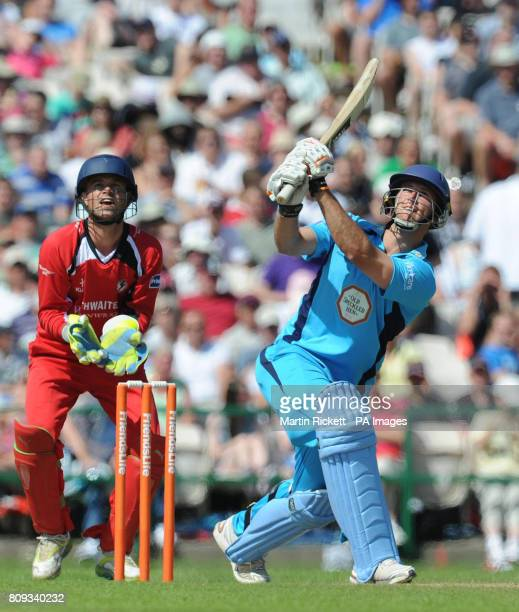 Derbyshire's Ross Whiteley hits out watched by Lancashire wicket keeper Gareth Cross during the Friends Life T20 match at Old Trafford Manchester