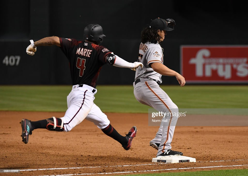 Dereck Rodriguez #57 of the San Francisco Giants gets a force out at first base as Ketel Marte #4 of the Arizona Diamondbacks lunges for the bag during the fourth inning at Chase Field on June 30, 2018 in Phoenix, Arizona.