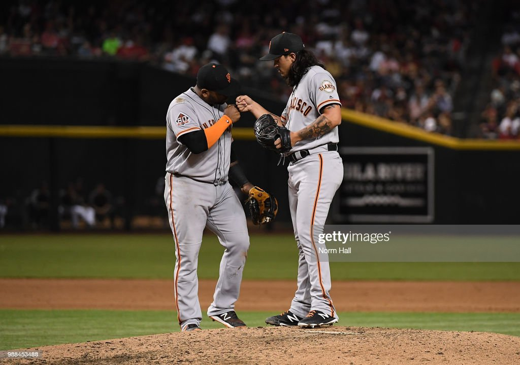 Dereck Rodriguez #57 of the San Francisco Giants is congratulated by teammate Pablo Sandoval #48 after being relieved during the seventh inning against the Arizona Diamondbacks at Chase Field on June 30, 2018 in Phoenix, Arizona.