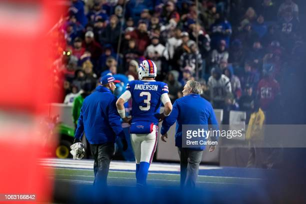 Derek Anderson of the Buffalo Bills is walked off the field by medical staff after being sacked in the team's final drive against the New England...