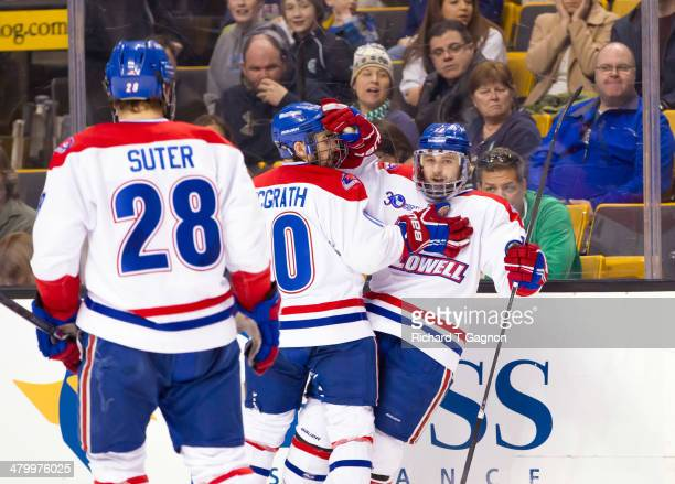 Derek Arnold of the Massachusetts Lowell River Hawks celebrates his goal with teammates Ryan McGrath and Jake Suter during NCAA hockey action against...