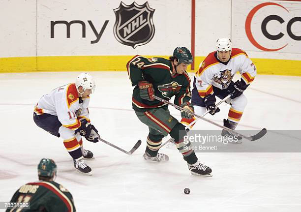 Derek Boogaard of the Minnesota Wild handles the puck against Gregory Campbell and Steve Montador of the Florida Panthers at the Xcel Energy Center...