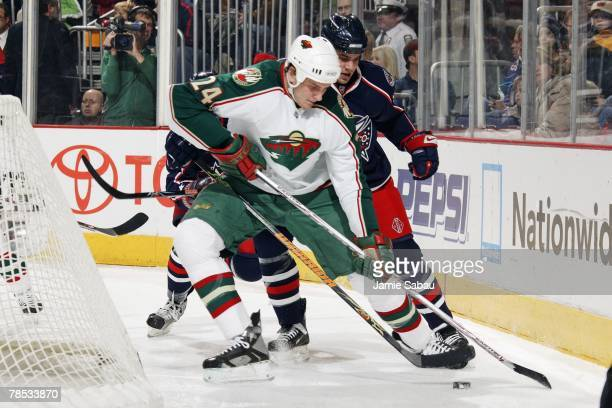 Derek Boogaard of the Minnesota Wild is defended by Rostislav Klesla of the Columbus Blue Jackets as Boogaard skates with the puck behind the net on...