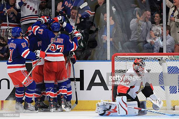 Derek Boogaard of the New York Rangers is congratulated by team mates after scoring a goal as Brian Elliott of the Ottawa Senators sits in the crease...