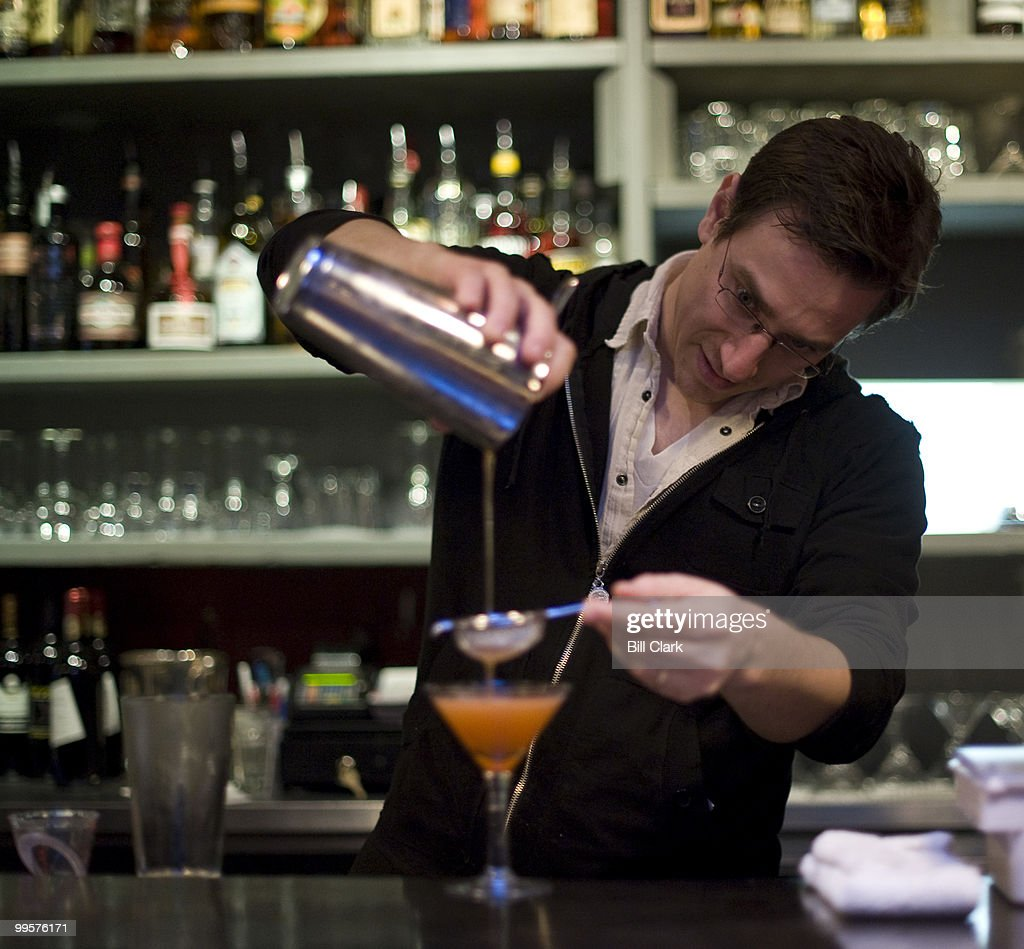 Derek Brown pours a Pink Gin drink behind the bar at The Passenger.