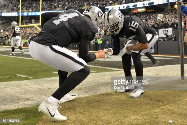 Derek Carr and Michael Crabtree of the Oakland Raiders celebrate after a touchdown against the Dallas Cowboys during their NFL game at OaklandAlameda...
