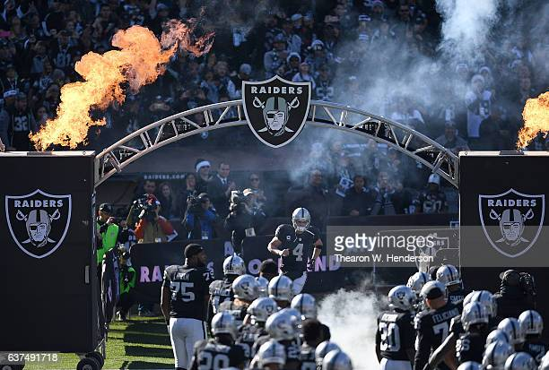 Derek Carr and the Oakland Raiders runs onton the field prior to playing the Indianapolis Colts in an NFL football game at the OaklandAlameda County...