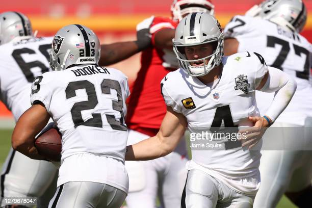 Derek Carr of the Las Vegas Raiders hands the ball off to Devontae Booker against the Kansas City Chiefs during the second quarter at Arrowhead...