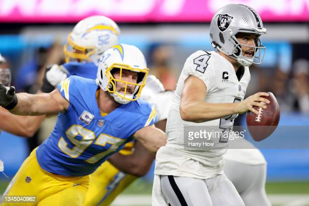 Derek Carr of the Las Vegas Raiders scrambles away from Joey Bosa of the Los Angeles Chargers during a 28-14 loss to the Chargers at SoFi Stadium on...
