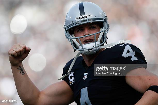 Derek Carr of the Oakland Raiders celebrates after a touchdown by Latavius Murray against the Carolina Panthers during their NFL game on November 27...