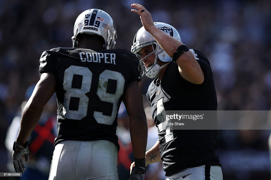 Derek Carr #4 of the Oakland Raiders celebrates with Amari Cooper #89 after a scoring on a two-point conversion against the San Diego Chargers during their NFL game at Oakland-Alameda County Coliseum on October 9, 2016 in Oakland, California.