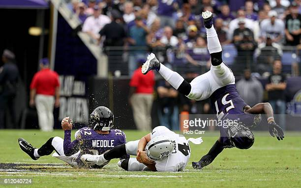 Derek Carr of the Oakland Raiders dives between CJ Mosley and Eric Weddle of the Baltimore Ravens in the second quarter at MT Bank Stadium on October...