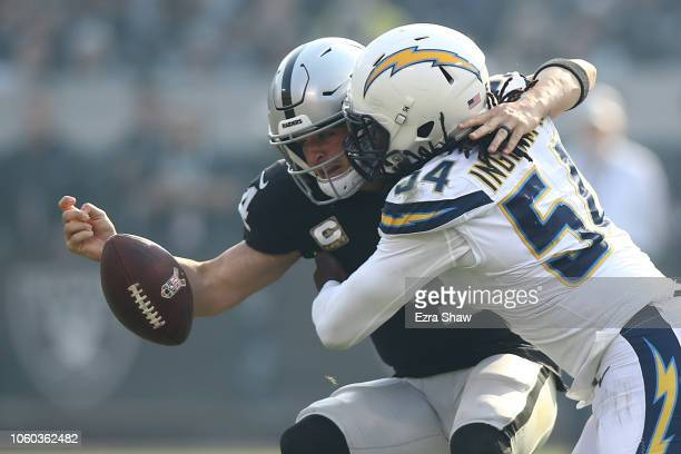 Derek Carr of the Oakland Raiders fumbles the ball after a hit by Melvin Ingram of the Los Angeles Chargers during their NFL game at Oakland-Alameda...