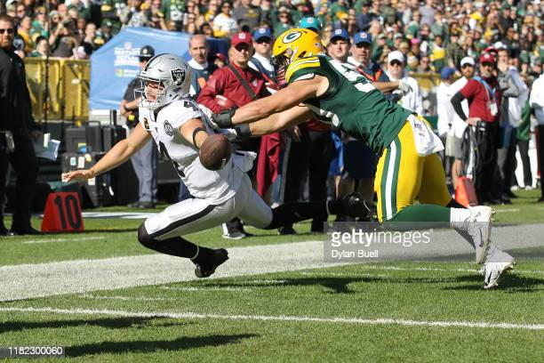 Derek Carr of the Oakland Raiders fumbles the ball as he dives for the pylon during the second quarter in the game at Lambeau Field on October 20...