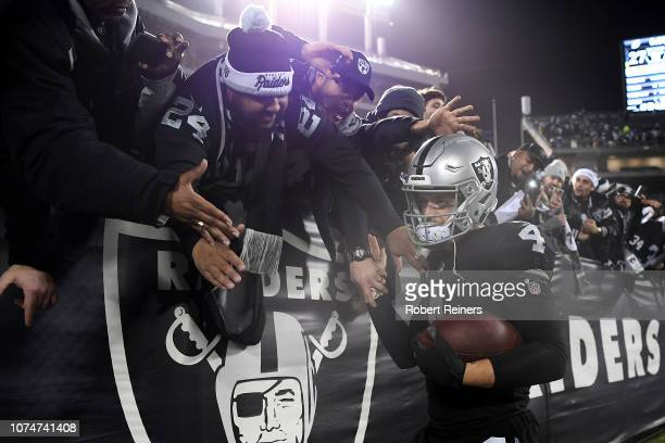 Derek Carr of the Oakland Raiders greets fans in the stands after their 2714 win over the Denver Broncos in what may be the final Raiders game at the...