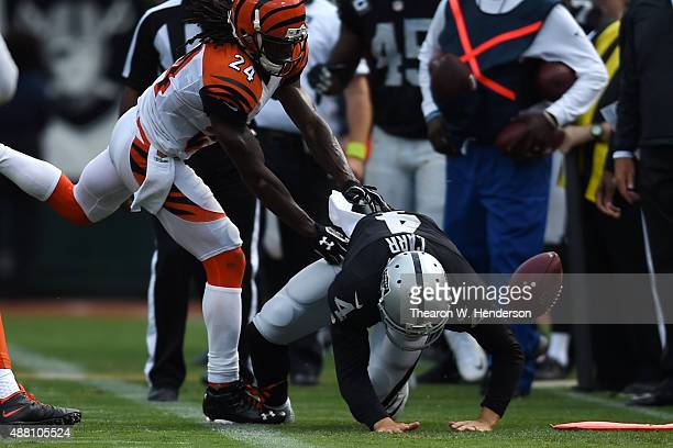 Derek Carr of the Oakland Raiders is hit by Adam Jones of the Cincinnati Bengals during the first half of their NFL game at Oco Coliseum on September...