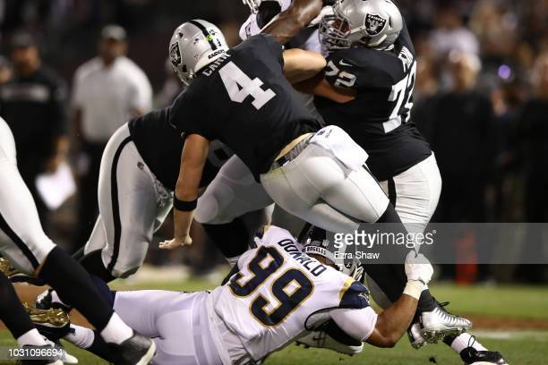 Derek Carr of the Oakland Raiders is hit low by Aaron Donald of the Los Angeles Rams during their NFL game at OaklandAlameda County Coliseum on...