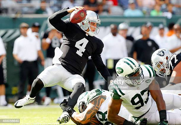 Derek Carr of the Oakland Raiders is sacked by Jason Babin of the New York Jets against the on September 7 2014 at MetLife Stadium in East Rutherford...