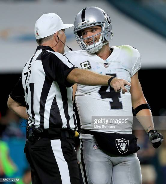 Derek Carr of the Oakland Raiders of the Oakland Raiders talks with an official during a game against the Miami Dolphins at Hard Rock Stadium on...