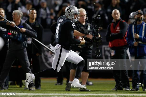 Derek Carr of the Oakland Raiders runs for 32yards against the Dallas Cowboys during their NFL game at OaklandAlameda County Coliseum on December 17...