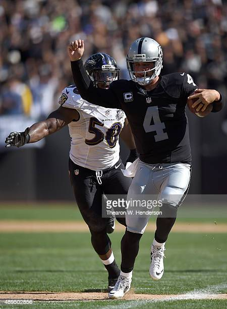 Derek Carr of the Oakland Raiders runs with the ball while pursued by Albert McClellan of the Baltimore Ravens in the third quarter at the Oco...