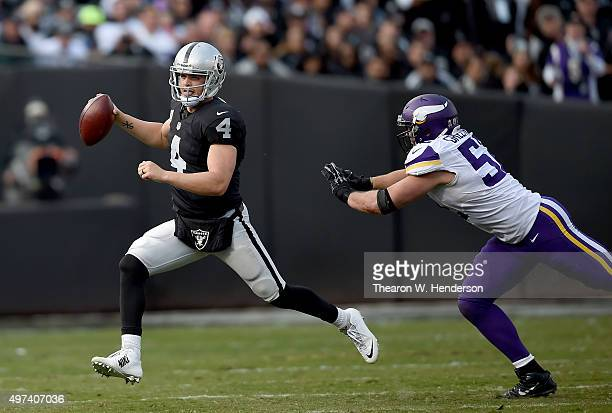 Derek Carr of the Oakland Raiders scrambles away from the pressure of Chad Greenway of the Minnesota Vikings during the third quarter of their NFL...