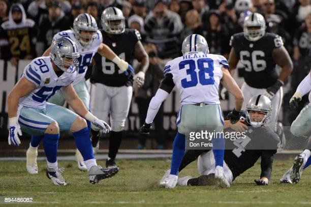 Derek Carr of the Oakland Raiders slides down against the Dallas Cowboys during their NFL game at OaklandAlameda County Coliseum on December 17 2017...